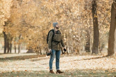 A photographer with a beard in an olive military cargo combat jacket, jeans, hat with backpack and wristwatch holds the DSLR camera, the smartphone and waits in the forest at the noon.