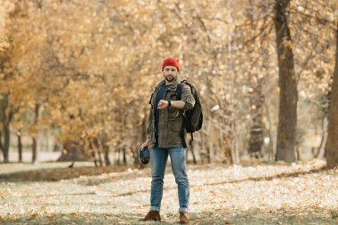 A photographer with a beard in an olive military combat cargo jacket, jeans, red hat with backpack holds the DSLR camera checks the time on the wristwatch in the forest at the afternoon