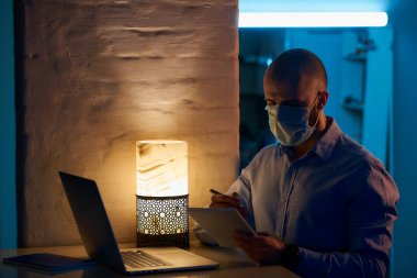 A man in a medical face mask to avoid the spread coronavirus working remotely on his laptop during the quarantine. A bald teacher works with a notebook from home during the pandemic of COVID-19.