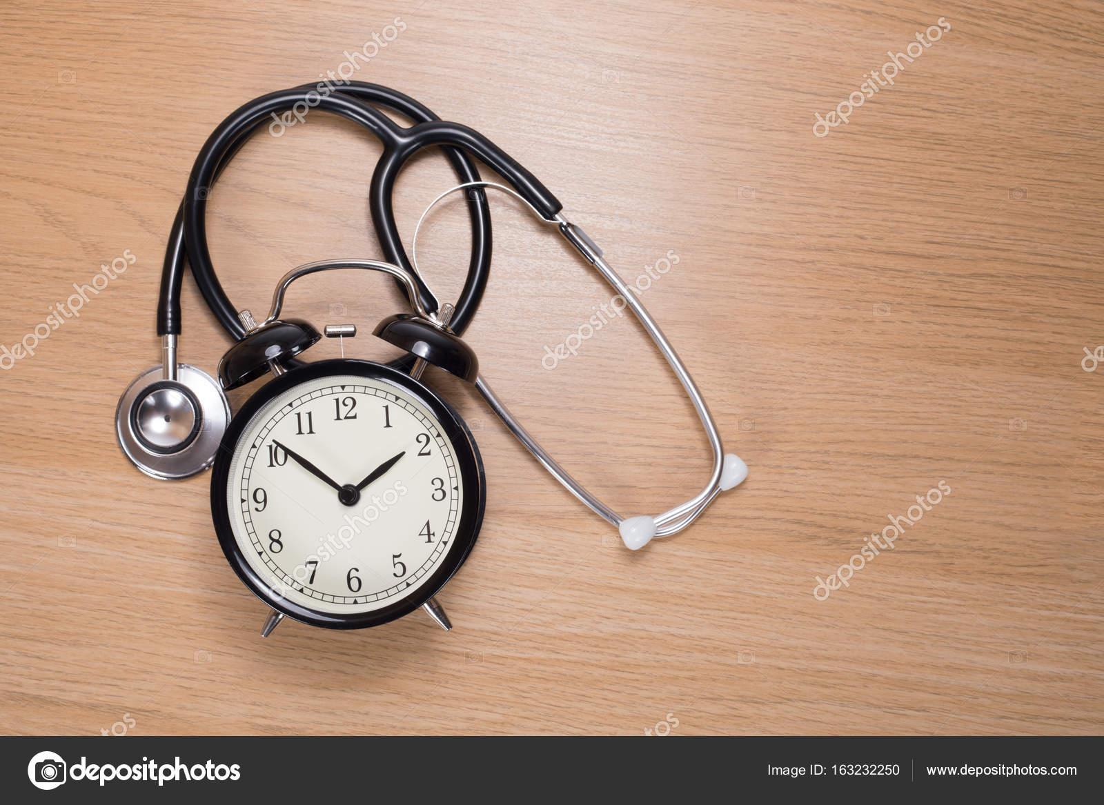 stethoscope with alarm clock lying on wooden desk stock photo