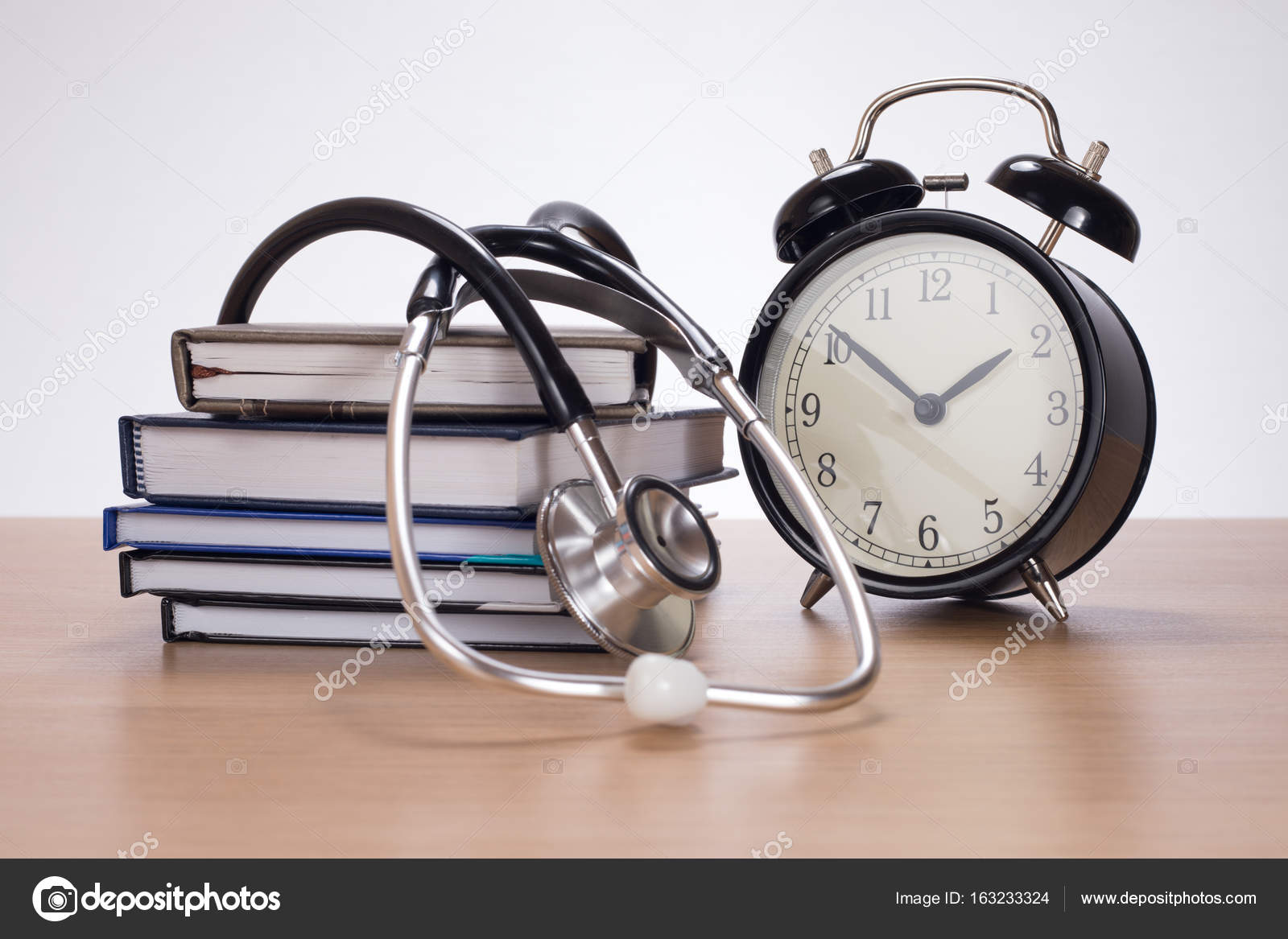 stethoscope among pile of planners and clock stock photo