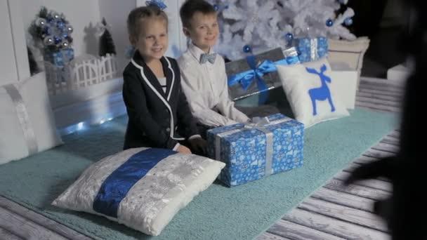 Kinder mit Geschenken am Weihnachtsbaum
