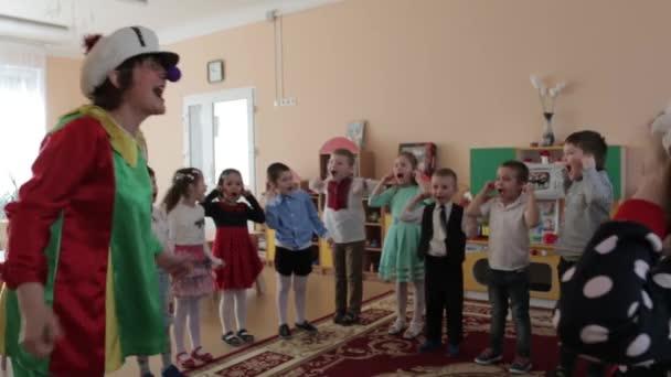 Happy clown plays with children in kindergarten.