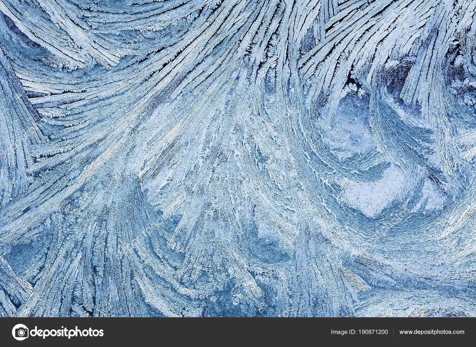 textura de patrón escarchado azul hermoso en el vidrio de invierno ...