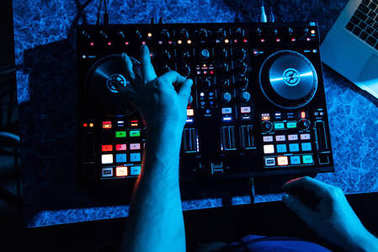 Hands of DJ and professional music equipment, mixer buttons and controlling levels of music