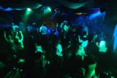 blurred silhouettes of people at concert on dance floor of night club with green lighting