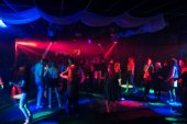 blurred silhouettes of dancing people in night club on the dance floor