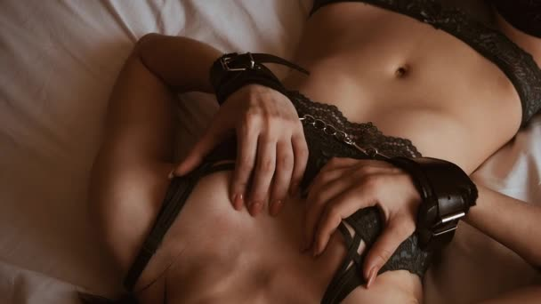 sexy junges Mädchen in Lederhandschellen genießt ihren Körper und streichelt ihre Brüste