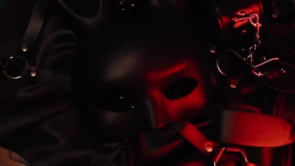 BDSM Set von erotischem Spielzeug aus einem Sexshop. Maske, Ledergürtel, Handschellen und Peitsche