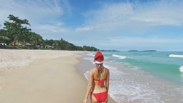 Krásná vánoční Kavkazský žena v santa čepice a červené bikiny vtipy a odpočinek na pláži s bílým pískem. Nový rok v džungli a moře sluneční světlo. Dovolená v tropech