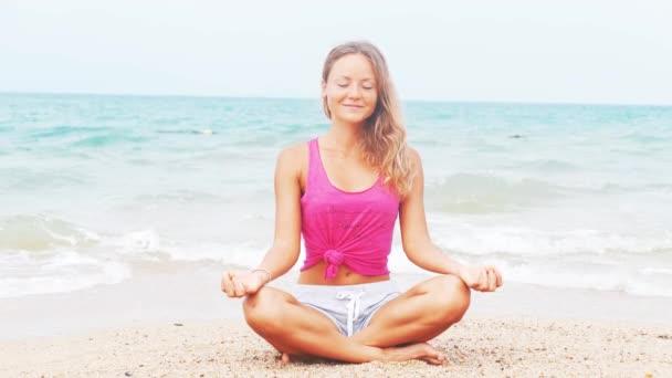 Žena, která dělá meditace v blízkosti ocean beach. Jóga silueta.
