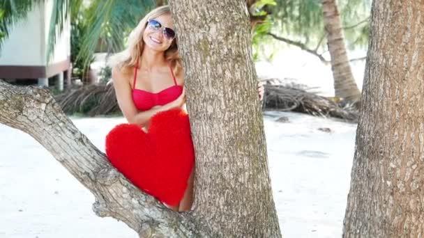 Krásná žena v červené bikiny na pláži u moře. Mladý Roztomilý dospívající dívka s hračkou srdce. Ostrov