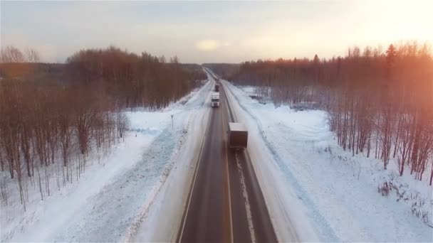 Many trucks drives on snow highway in sunsets.