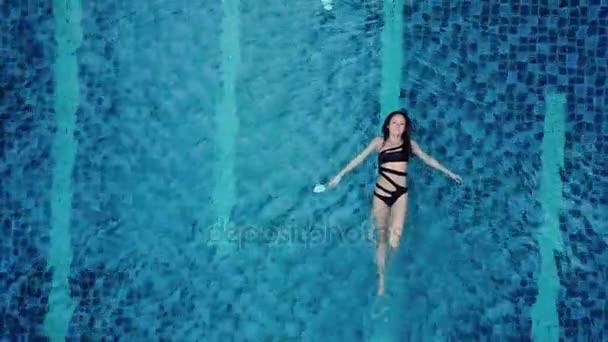 Luftbild von oben: Ein verführerisch sexy Model in schwarzer Badebekleidung genießt die Entspannung im Hotelpool. erstaunliche Mode Frau im Bikini mit Luxus-Wellness-Erholung