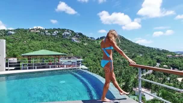 Zeitlupe. schöne Frau zu Fuß um Pool. schöner Meerblick von der Luxusvilla.