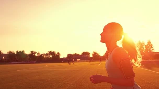 Běžec běží na předměstí, zdravé fitness wellness vitality sportovec silueta proti sluneční erupce. Mladá žena běží na stadionu při západu slunce