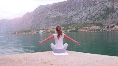 Beautiful yoga with amazing view of sea on background, pretty healthy woman with perfect body stand in one of yoga pose