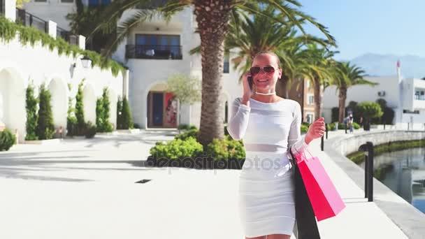 Lassú mozgás. Napszemüvegek a gyönyörű nő a gazdaság bevásárló táskák, használ egy okos telefon, és mosolyogva, miközben állandó szabadban