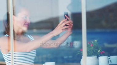 Smiling young woman maiking selfie in cafe shop