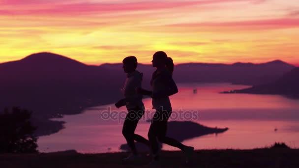 Běh - dvě ženy běžec běhání při západu slunce