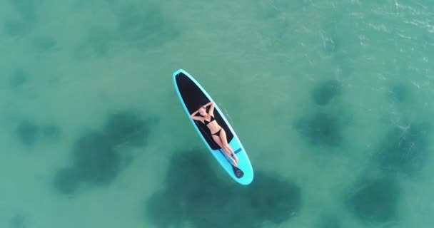 Camera moving around Attractive woman in bikini is sunbathing on a surfboard, aerial view