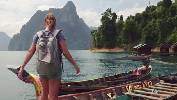 Woman going to go travel by traditional thai style boat at Khao Sok park. Thailand