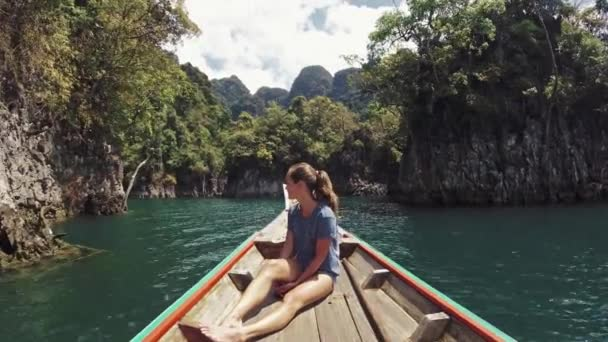 Graceful woman with long legs relaxing on boat enjoying wild nature on long tail boat trip at Khao Sok national park . Excursion in Thailand. Beautiful traveler girl on tropical vacation .