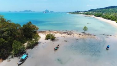 AERIAL. Drone flying under the amazing tropical bay with clear water, white beach and traditional longtail boats. Trquoise water. Paradaise island, Thailand.