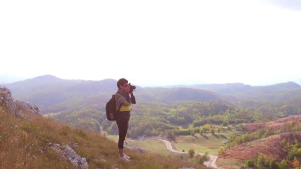 fiatal nő fotós figyelembe fotó a hegycsúcs