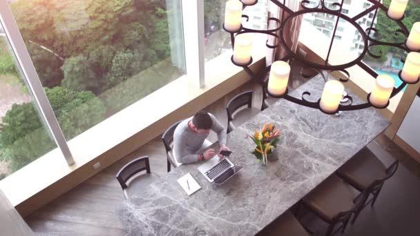 Az ember a nagy íróasztal felülnézet. Tiszta működő hely a hatalmas tábla üzletember dolgozik laptop, használ smartphone és írásban valami-hoz jegyzetfüzet. Nagy windows-háttér