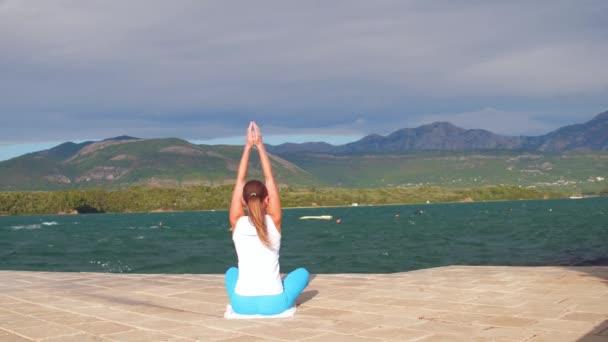 Fiatal lány jóga póz a mólón. Sport nő blu és fehér ruhát jóga mountan kilátással az Adriai-tenger, az Európai weared.