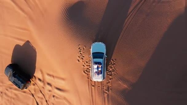 Letecký. Horní pohled na mladý pár relaxaci na střeše auta v poušti