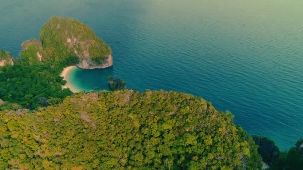 AERIAL. Top view of green island and beach with traditional thai boat at the sunset.