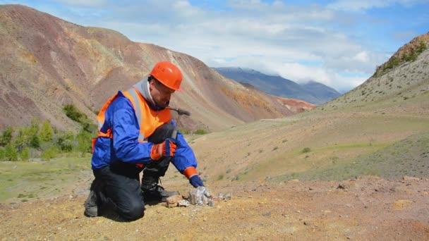 geolog klepněte na skalní útvar s kladivem