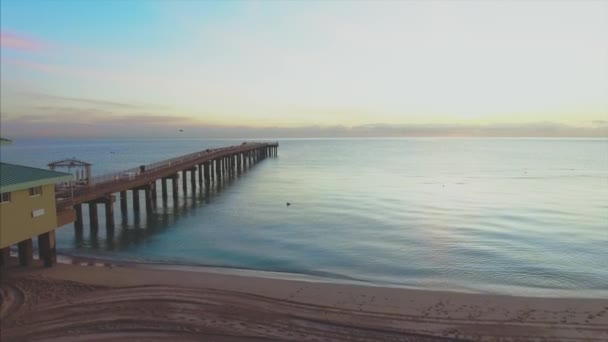 Letecký náklon nahoru molo na pláži na Floridě při východu slunce