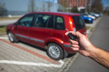 Man driver unlocking the car remotely by the car key, transport concept