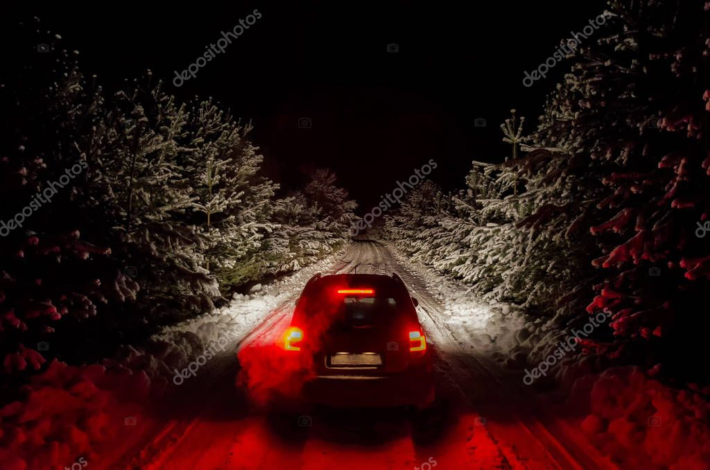 The car rides in the evening on a winter road in the woods.