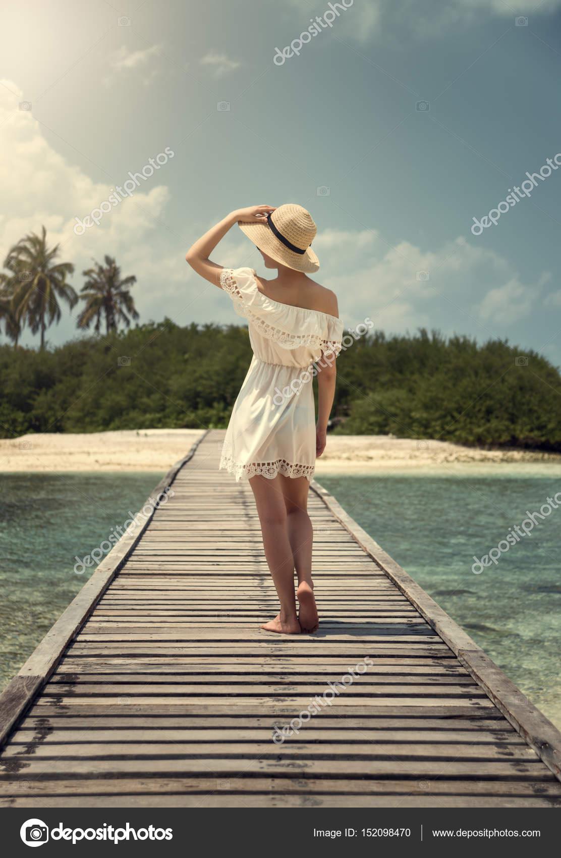 Eine Mädchen in einem weißen Kleid und Hut steht auf einer Brücke ...