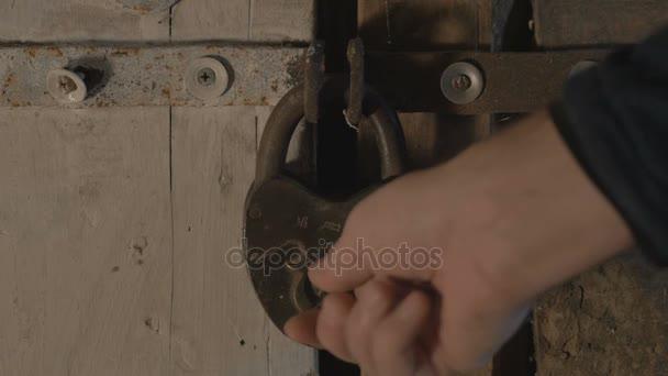 männlicher Metallschlüssel entriegelt das Vorhängeschloss, öffnet die Holztür und tritt ein