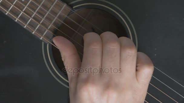 Detailní záběr struny kytary. Člověk hraje gitare