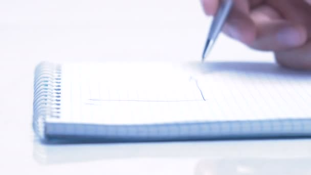 Male hand is writing in business document lying on the table. Close-up.