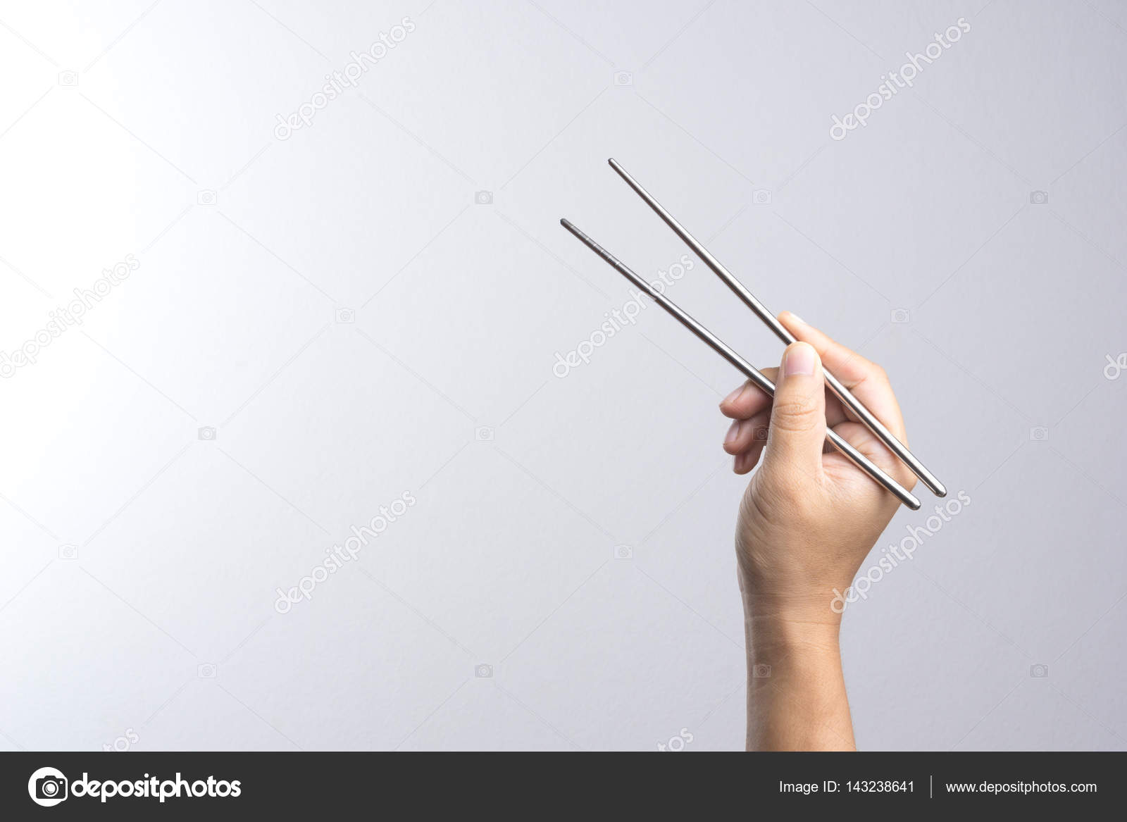 Hand Holding Stick ~ Hand holding stainless chop stick — stock photo