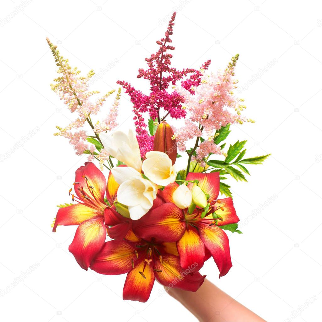 Flowers of lily, ixia and astilbe in a bouquet hold in hand isol