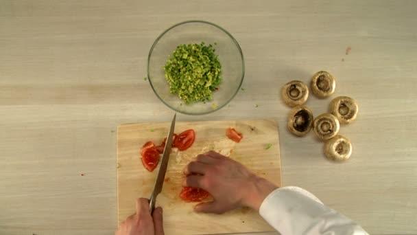 Vaření potravin. Pohled shora šéfkuchaře jemně dělené rajče