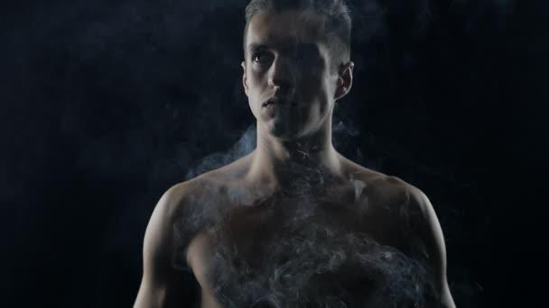 Handsome shirtless man standing on dark background, with smoke around him.