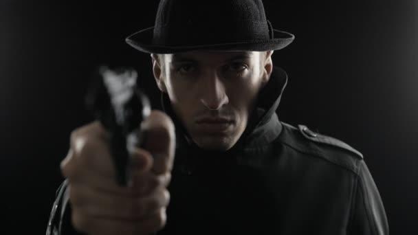 Porträt eines Gangsters mit Hut und schwarzem Umhang bedroht Waffe