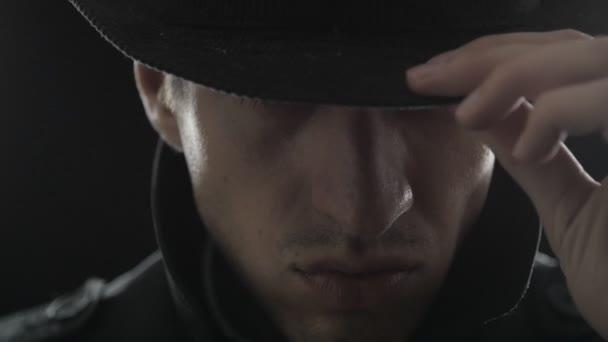 Nahaufnahme Porträt eines Gangsters mit Hut und schwarzem Mantel
