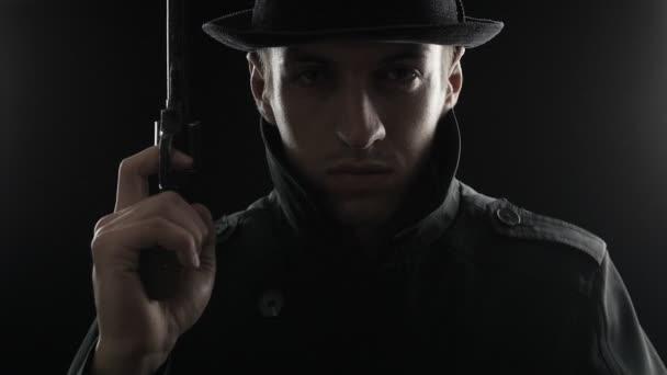 Porträt eines Mafioso mit Hut und schwarzem Mantel mit Pistole in der Hand