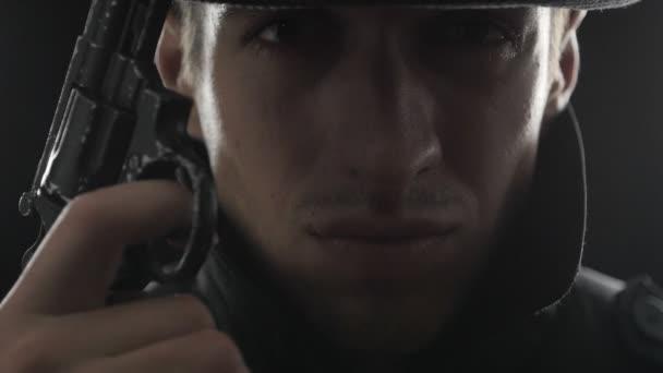 Nahaufnahme Porträt eines Gangsters mit Hut und schwarzem Mantel mit Waffe