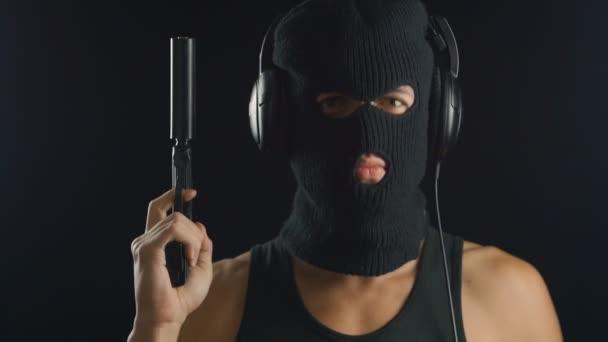 muž v kuklu a košili A se zbraní poslechu hudby ve sluchátkách